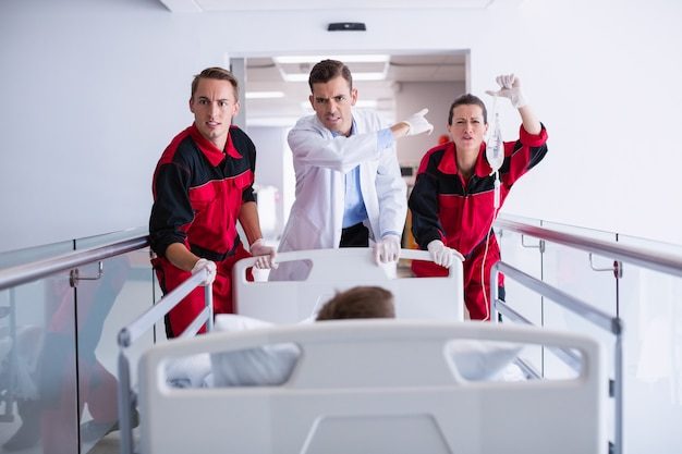 Doctors pushing emergency stretcher bed in corridor
