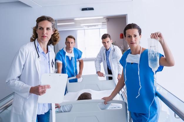 Doctors pushing emergency stretcher bed in corridor