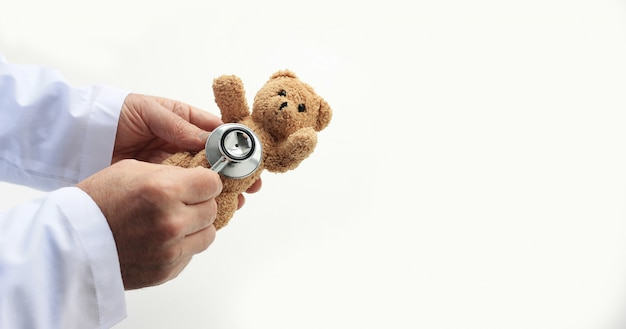 Doctors's hands holding toy teddy bear and putting stethoscope's close to it.