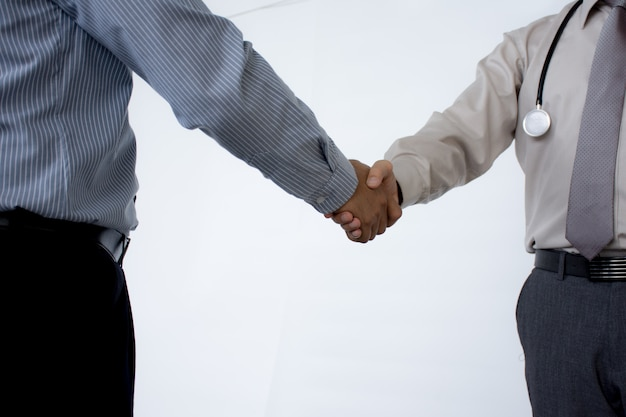 Doctors shaking hands to each other finishing up medical meeting  isolated on gray background.