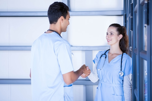 Doctors shaking hands in hospital corridor