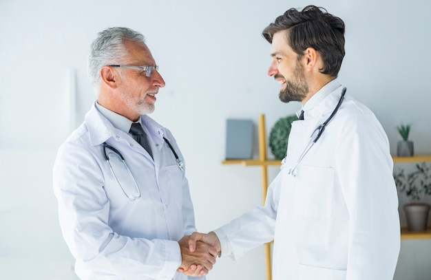 Doctors shaking hands and looking at each other