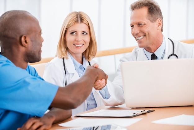 악수 하는 의사. 여의사와 함께 앉아 악수하는 두 명의 쾌활한 의사