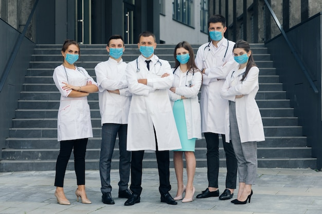Doctors stand with arms crossed while wearing protective face masks outdoors during covid-19 epidemic and looking at camera.