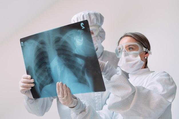 Врачи, стоящие на белой стене, исследуют рентгеновский снимок пневмонии у пациента с covid-19 в клинике. концепция коронавируса.