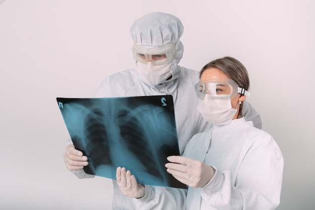 Doctors standing on white background examine x-ray for pneumonia of a covid-19 patient in the clinic. coronavirus concept.