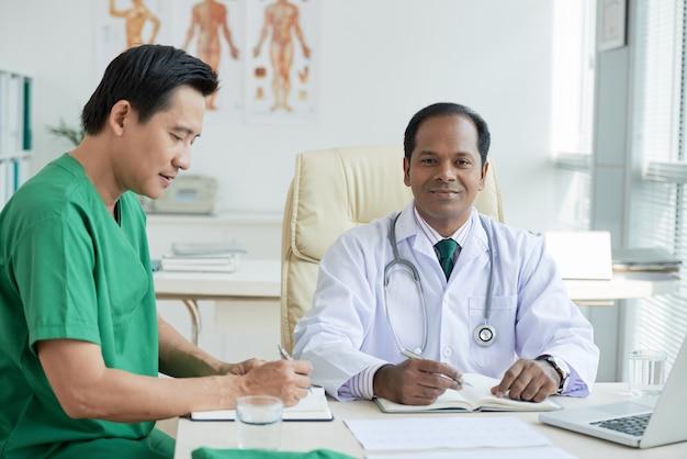 Врачи делают заметки в планировщиках при работе за столом в медицинском кабинете