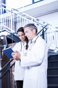 Doctors using digital tablet on staircase in hospital