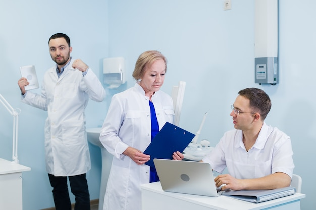 Doctors using a laptop, discussing diagnosis while standing in clinic