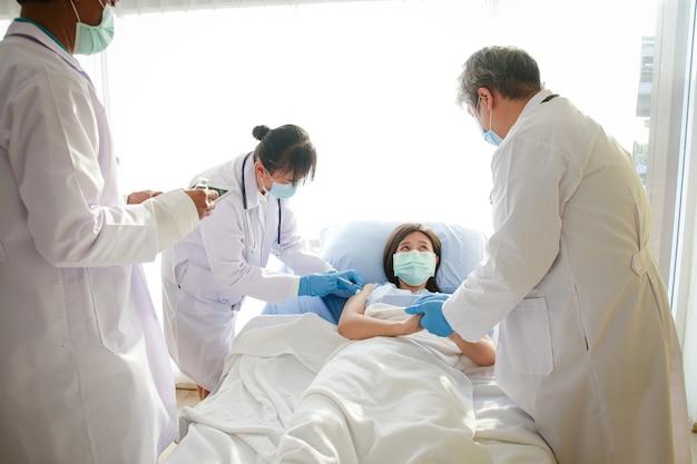 병원 침대에 누워있는 마스크를 쓰고있는 아시아 여성의 코로나 바이러스 예방 접종 의사