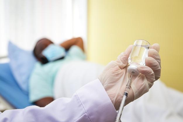 医師は手袋を着用して、アフリカ系アメリカ人の男性にコロナウイルスの予防接種を行います。免疫力を高めるため。病院医療サービスの概念