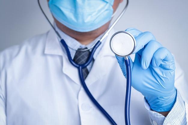 マスクと青い手袋を着用している医師。聴診器を持って患者を診察します。医療サービスの概念、コロナウイルスを治します。