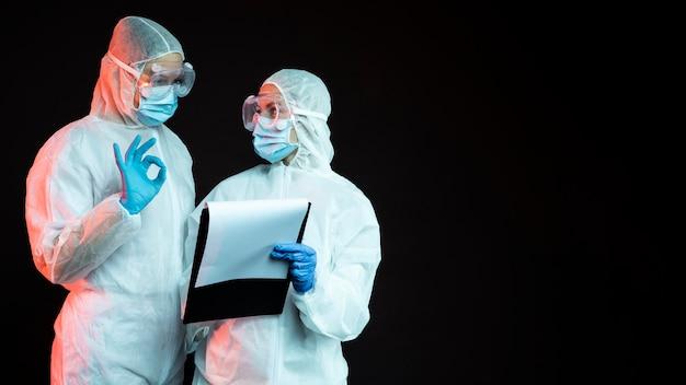 Medici che indossano abbigliamento medico pandemico con copia spazio