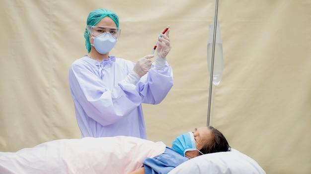 의사들은 노인 환자의 혈액 샘플을 수집하기 위해 튜브를 들고 마스크를 쓰고 있었다