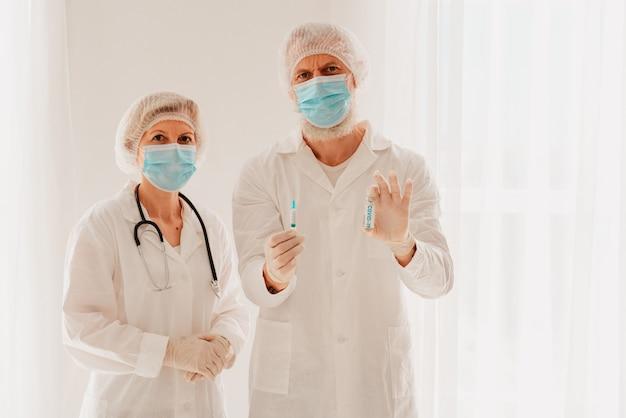 안면 마스크를 쓴 의사들은 코비드-19 바이러스에 대한 백신으로 일할 준비가 되어 있습니다