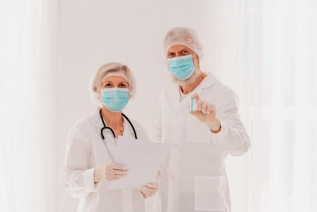 안면 마스크를 쓴 의사들은 코비드 바이러스에 대한 백신으로 일할 준비가 되어 있습니다