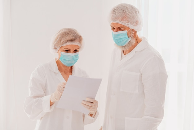 안면 마스크를 쓴 의사들이 병원에서 함께 일한다