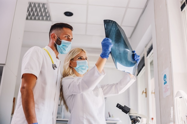 Врачи в масках для лица и в резиновых перчатках смотрят на рентгеновский снимок легких.