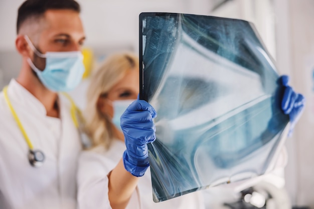 얼굴 마스크와 고무 장갑을 가진 의사는 폐의 x- 레이를보고 있습니다.