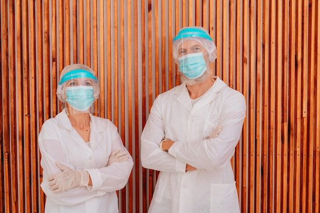 마스크와 얼굴 보호기를 가진 의사는 병원에서 일할 준비가되어 있습니다