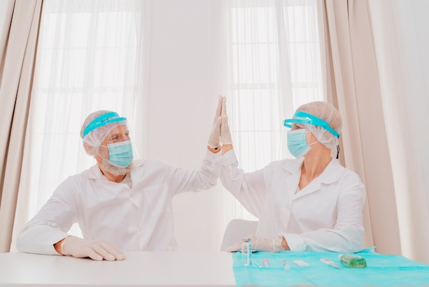 마스크와 얼굴 보호기를 쓴 의사들이 병원에서 일할 준비가 되어 있다