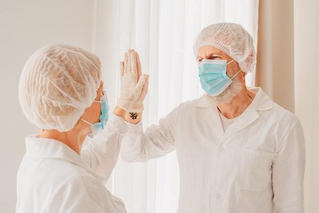 마스크와 얼굴 보호기를 착용 한 의사는 손으로 서로에게 5 점을줍니다.
