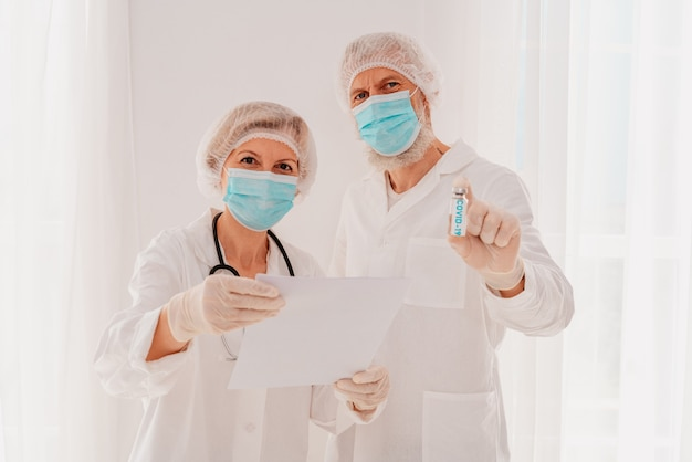 마스크를 쓴 의사들은 코비드 바이러스 백신을 보여줍니다