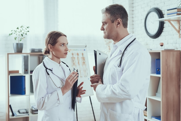 Doctors with stethoscopes in white gowns are talking