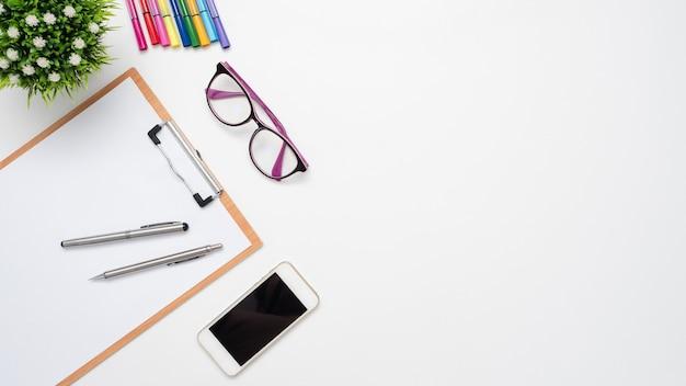 テーブルトップビューのコピースペースに携帯電話のメガネカラーペン花瓶とドキュメントボードとペン
