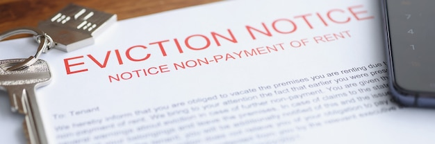 Document on eviction from housing for nonpayment lies on table with keys