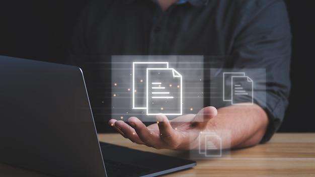 Концепция управления документами. бизнесмен, работающий с портативным компьютером с иконами на виртуальном экране.