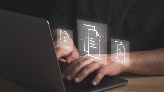 Document management concept.businessman working with laptop computer with icons on virtual screen.
