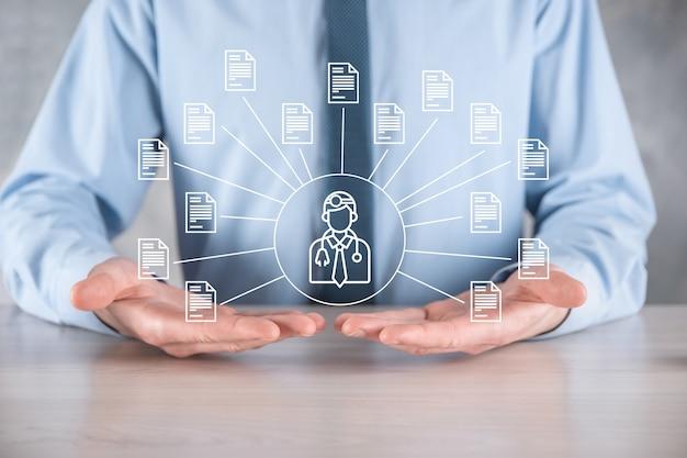 Система управления документами dms. деловой человек держит врача и значок документа. программное обеспечение для архивирования,