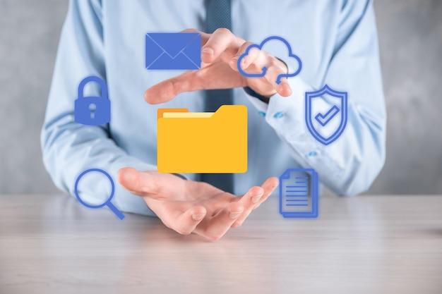 ドキュメント管理システムdms。ビジネスマンはフォルダとドキュメントアイコンを保持します。企業のファイルと情報をアーカイブ、検索、管理するためのソフトウェア。インターネット技術の概念。デジタルセキュリティ