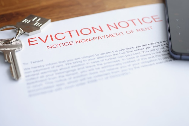 Документ о выселении из жилья за неуплату лежит на столе с ключами.