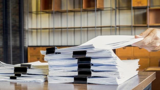ドキュメント、紙、ファイル。暗い木製のテーブルに置かれた紙の山。
