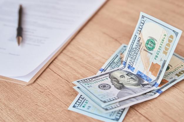 Документ, ручка и долларовые купюры на столе крупным планом