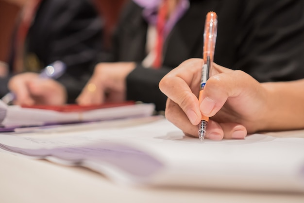 Document report and business busy concept: businesswoman manager hands holding pen for checking and signing white documents reports papers of paper files in modern office home background.