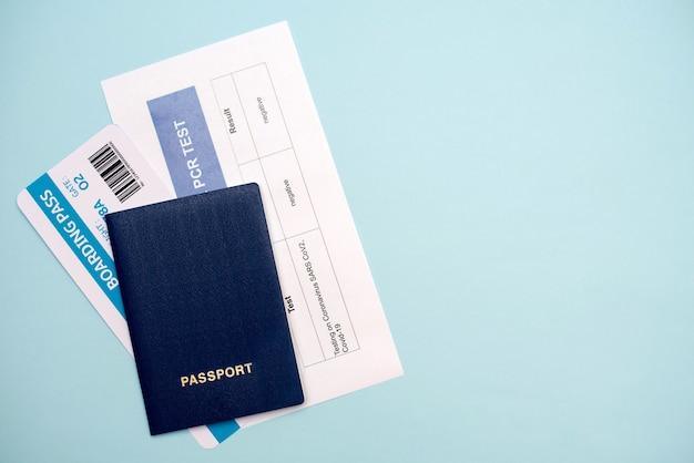 Covid-19流行中の空の旅の文書:パスポート、チケット、covid-19 pcrテスト、クローズアップ。
