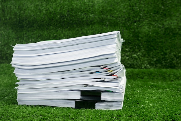Documents pile on grass in concept save earth and use paper economically