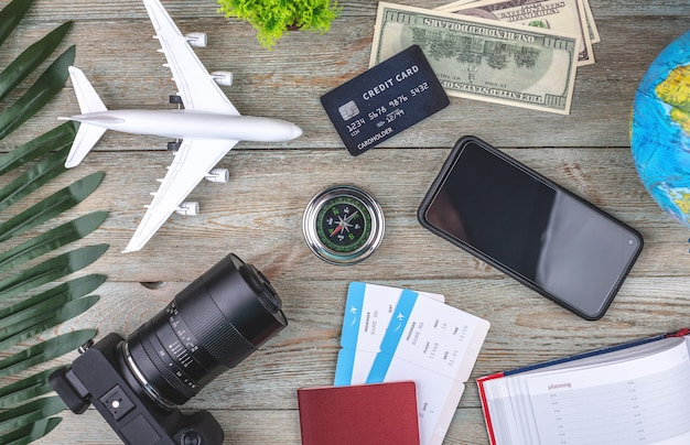 Documents, plane tickets and other travel supplies on a wooden background