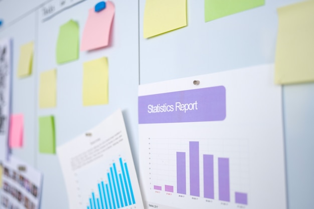 Documents with graphs of statistical reports and colorful stickers hanging on chalkboard in educatio...