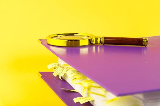 オフィス フォルダーに付箋のブックマークと黄色の壁に虫眼鏡が付いたドキュメント。スペースをコピーします。