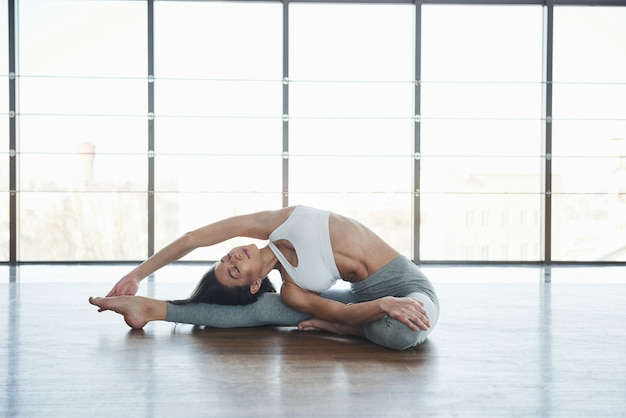 Does exercises for stretching. european young brunette doing yoga in the room with big windows