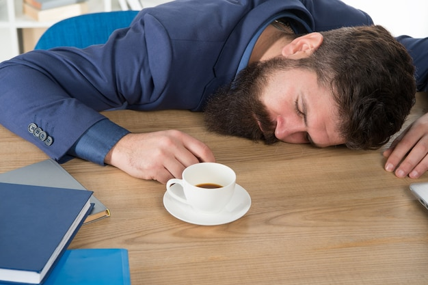 Does not help. man handsome boss sleep in office drinking coffee. comfy workspace. hard morning. bearded hipster formal suit relaxing with coffee. office life routines. first coffee. sleepless night.