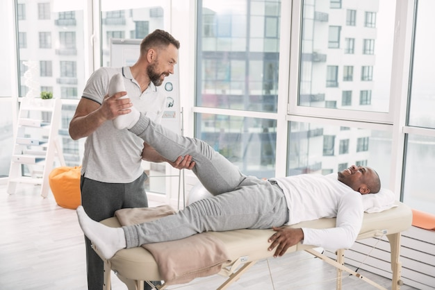Does it hurt. cheerful skilled man lifting the leg of his patient while trying to develop the muscles