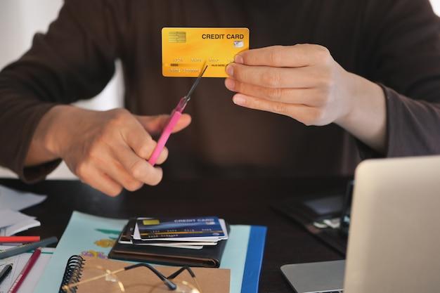 男の手がハサミを使用してクレジットカードをカットし、借金の返済の概念が消え、ワークデスクでのクレジットカードの使用を停止し、クレジットカードの浅いdofに焦点を当てる