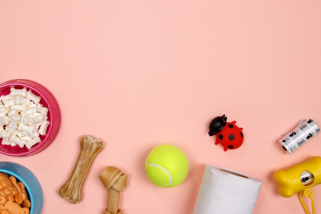 Dog accessories, food and toy on pink background. flat lay. top view.