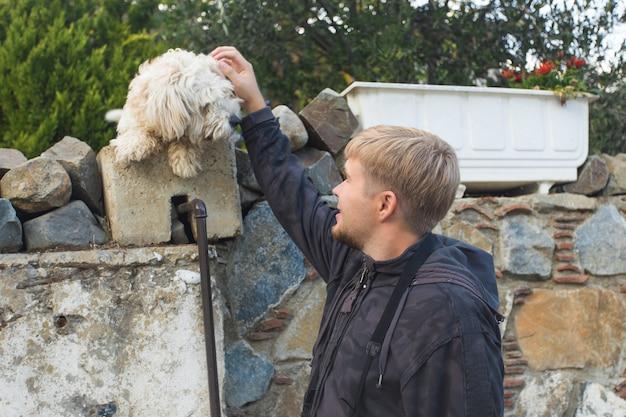 Собака и человек - собака и молодой человек веселятся в парке - концепции дружбы, домашних животных, единения
