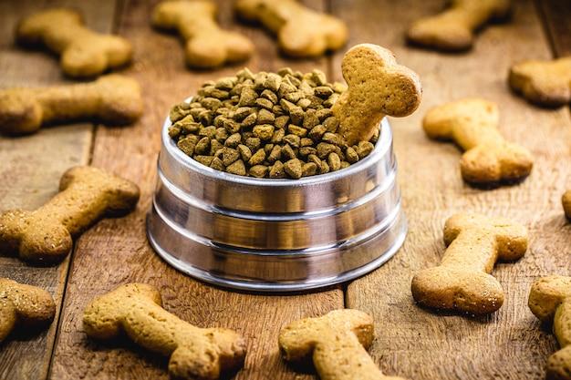 Собачье печенье в форме кости с банкой с едой, закуски для собак в деревенской обстановке, рожок для кормления домашних животных